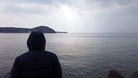 Een mens in een matroos met een kap die het zeegezicht bekijken Vladivostok, Primorsky Krai stock video