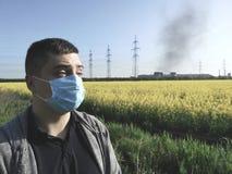 Een mens in een medisch masker tegen de achtergrond van de installatie Het concept milieuvervuiling, ecologie royalty-vrije stock foto's