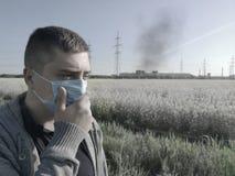 Een mens in een medisch masker tegen de achtergrond van de installatie Het concept milieuvervuiling, ecologie stock afbeelding