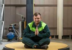 Een mens mediteert na het werk van een harde dag stock afbeelding