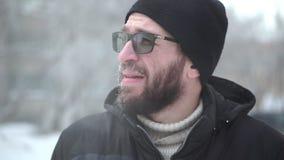Een mens met een baard en glazen onderzoekt de camera, rijp stock video