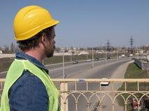 Een mens met een baard en een snor in een helm bevindt zich op de brug tegen de achtergrond van de weg De arbeider van de wegdien royalty-vrije stock foto's