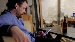 Een mens met een baard en een snor zit bij de lijst schrijvend sms op zijn telefoon, en op de lijst voor hem zijn twee flessen stock video