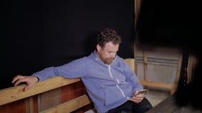 Een mens met een baard en een snor zit bij de lijst schrijvend sms op zijn telefoon, en op de lijst voor hem zijn twee flessen stock footage