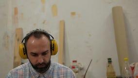 Een mens met een baard luistert aan muziek op hoofdtelefoons en zingt stock footage