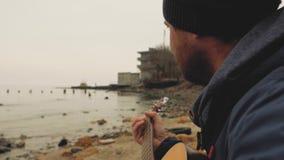Een mens met een baard maakt een foto van het overzees op cameraakerel met een baard en een hoed spelend een gitaar dichtbij het  stock video