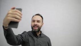 Een mens met een baard maakt een selfie op de telefoon stock video