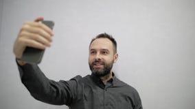 Een mens met een baard maakt een selfie op de telefoon stock footage