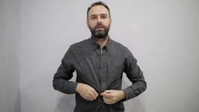 Een mens met een baard rekt zijn overhemd uit stock videobeelden