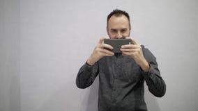 Een mens met een baard schiet video op de telefoon stock video