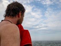 Een mens met een baard veegt van een handdoek na het zwemmen in het overzees af Achter mening royalty-vrije stock fotografie