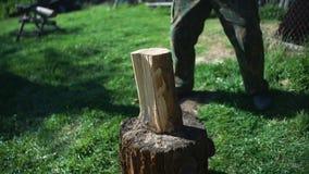 Een mens met een bijl hakkend hout stock footage