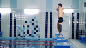 Een mens met een bionisch been rekt spieren uit om in de pool te springen stock video