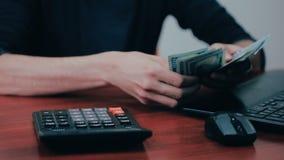 Een mens met calculator en rekeningen die geld tellen Financiën, zaken, economie stock footage