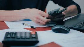 Een mens met calculator en rekeningen die geld tellen Financiën, zaken, economie stock video