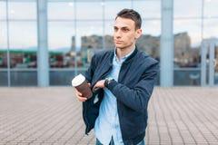 Een mens met een document Kop van koffie, gaat door de stad, een knappe kerel in modieuze kleren, terugtrekt zijn telefoon van zi stock foto's