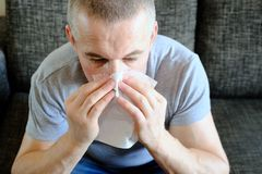 Een mens met een document zakdoek dichtbij zijn neus Allergieën, de lentebloei Reactie op stuifmeel, allergisch syndroom royalty-vrije stock fotografie