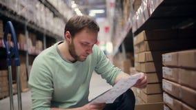 Een mens met een baard in een blauwe sweater die zijn lijst in een pakhuis controleren stock videobeelden