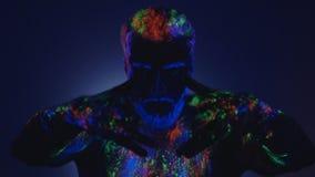 Een mens met een baard in het ultraviolette licht Magische passen met handen stock videobeelden