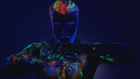 Een mens met een baard in het ultraviolette licht Magische passen met handen Close-up van handen Dans in ultraviolet licht  stock videobeelden