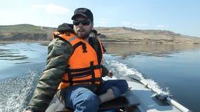 Een mens met een baard zwemt op een pvc-boot door de rivier stock video