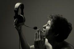 Een mens met een hoofdtelefoon zegt zacht in de microfoon Royalty-vrije Stock Afbeeldingen