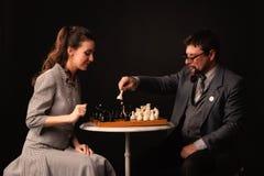 Een mens met een meisje speelt schaak en rookt een pijp op een donkere backgr Stock Afbeelding