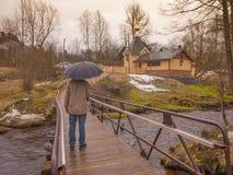 Een mens met een paraplu gaat naar kerk op een brug Stock Afbeeldingen