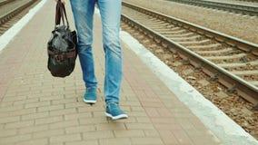 Een mens met een reiszak gaat langs de spoorweg Slechts zijn de benen zichtbaar in het kader steadicam schot stock videobeelden