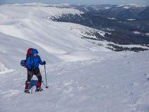 Een mens met een rugzak en sneeuwschoenen Royalty-vrije Stock Foto's