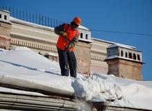Een mens met een schop verwijdert sneeuw uit een dak Stock Fotografie