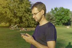Een mens met een smartphone in het park Stock Afbeeldingen