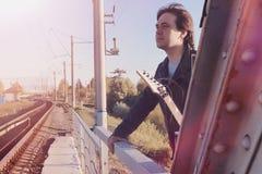 Een mens met een elektrische gitaar op de spoorweg Een musicus in le Stock Afbeeldingen