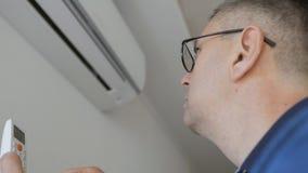 Een mens met glazen die een afstandsbediening houden en de airconditioning thuis aanzetten Gespleten systeem in bijlage aan stock footage