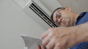 Een mens met glazen die zich naast een werkende airconditioner bevinden bestudeert het instructiehandboek van het apparaat stock video