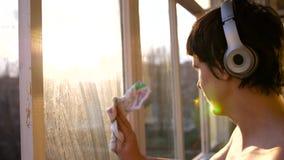 Een mens met hoofdtelefoons die aan muziek luisteren en het venster in de flat wassen Vensterreinigingsmachine stock videobeelden