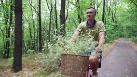 Een mens met een kind die een fiets in het bos, in de zomer berijden, het kind zit als speciale voorzitter stock video