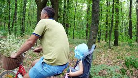 Een mens met een kind die een fiets in het bos, in de zomer berijden, het kind zit als speciale voorzitter stock videobeelden