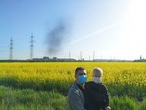 Een mens met een kind in van hem dient medische maskers op de achtergrond van de installatie in Het concept milieuvervuiling, eco royalty-vrije stock fotografie