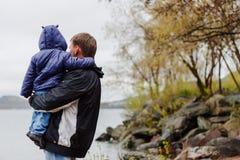 Een mens met een kind in zijn wapens bevindt zich op het meer royalty-vrije stock fotografie