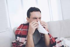 Een mens met een koude zit op de laag, die achter een rode deken verbergen Hij blaast zijn neus in een servet stock afbeelding