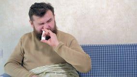 Een mens met een koude zit op de laag Hij bestrooit een speciale neusnevel in zijn neus stock footage