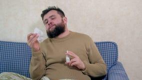 Een mens met een koude zit op de laag Hij bestrooit een speciale neusnevel in zijn neus stock videobeelden
