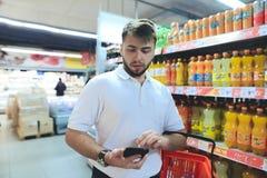 Een mens met een mand bekijkt de telefoon terwijl het winkelen bij een supermarkt Het winkelen in de opslag royalty-vrije stock fotografie