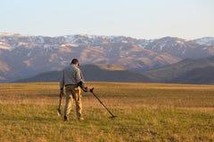 Een mens met een metaaldetector op zoek naar een schat stock afbeeldingen