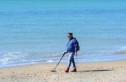 Een mens met een metaaldetector zoekt dure die juwelen in het overzees worden verloren Een mens loopt langs het strand op zoek na stock fotografie