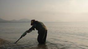 Een mens met een metaaldetector zoekt waardevolle punten op het strand stock videobeelden