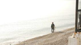 Een mens met een metaaldetector zoekt waardevolle punten op het strand bij dageraad in mist stock videobeelden