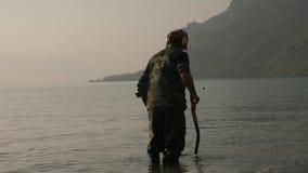 Een mens met een metaaldetector zoekt waardevolle punten op het strand bij dageraad in mist op achtergrond van klippen stock footage