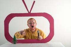 Een mens met rood haar, een baard en een snor in een geel overhemd, glazen parodieert de voorzitters` s toespraak op televisie Ke Stock Fotografie